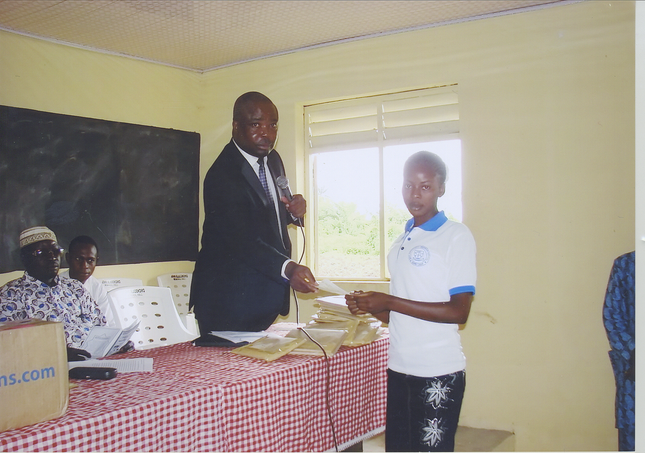 Female Students Receiving An Award From Barrister Folade