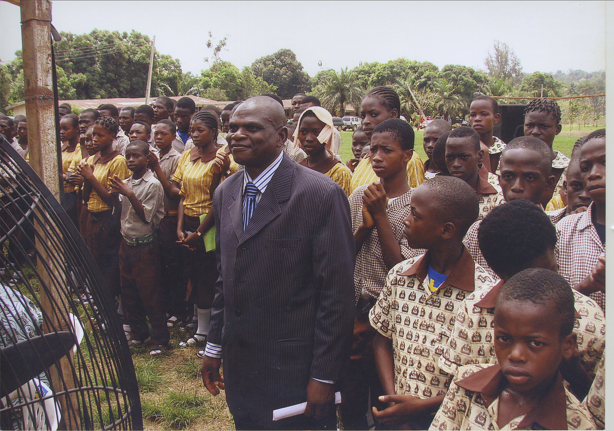 Principal Ajamu Of The Community Grammar School Surrounded By His Students